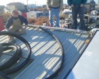 David Lindeen (Susitna Energy Systems) unravels the solar thermal line set on Enock Sheidt's house, while Claude Wilson (KEA) and Mark Kulner supervise.
