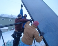 Workers from Alaska Battery Systems and Claude Wilson (KEA) raise a flat plate solar thermal panel on MaryAnn Mendenhal's house.