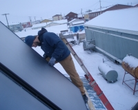 Jesse Logan (KEA) adjusts a flat plate solar thermal panel on Mary Omnik's house.
